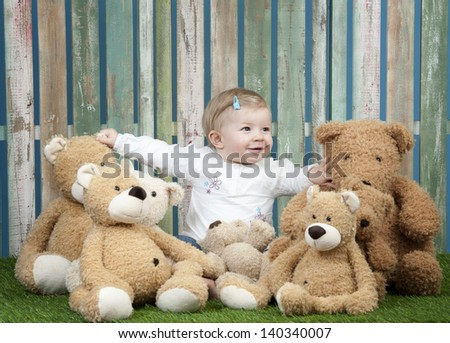 baby girl with group of teddy bears, seated in front of a fence - stock photo