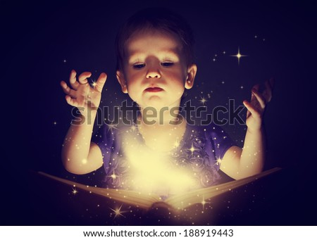 baby girl with magic book on a dark background - stock photo