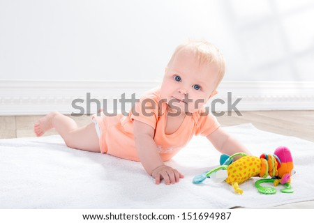 baby girl  with toy in the hand, lying on the floor - stock photo