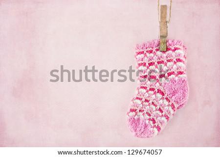 Baby girl woolen socks on textured pastel pink background - stock photo