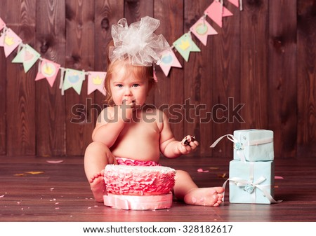 Baby girl 1 year old eating birthday cake in room. Birthday party. Looking at camera. Childhood.  - stock photo