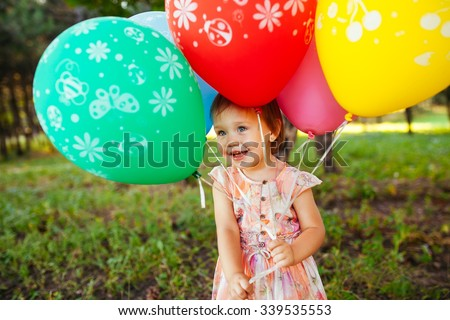 Baby girl 2-3 year old holding balloons outdoors. Birthday party. Childhood. Happiness.  - stock photo