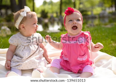 Baby girls playing in park - stock photo