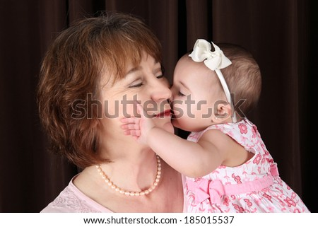 Baby granddaughter giving grandmother a kiss on the cheek - stock photo
