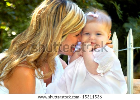 Baby grins as mom nuzzles her cheek.  White wooden picket fence in background. - stock photo