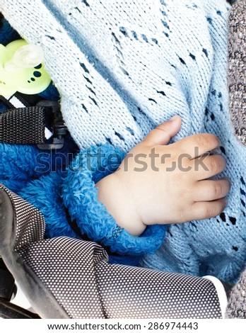 Baby hand baby sleeping in stroller - stock photo