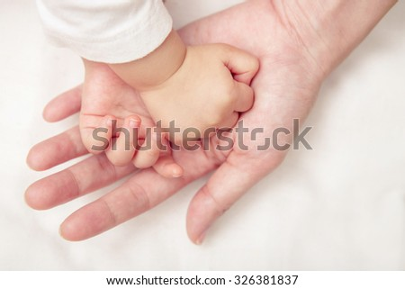 Baby hand gently holding adult's finger (Soft focus and blurry) - stock photo