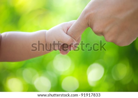 Baby hand hold father hand - stock photo