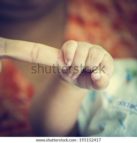 baby hand holding Rough finger - stock photo