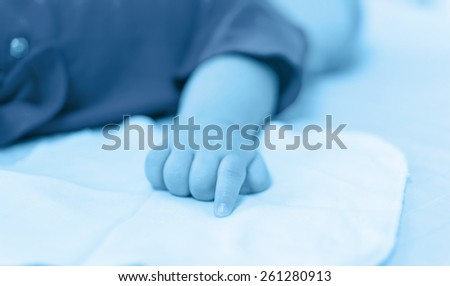 baby hand on the bed - stock photo