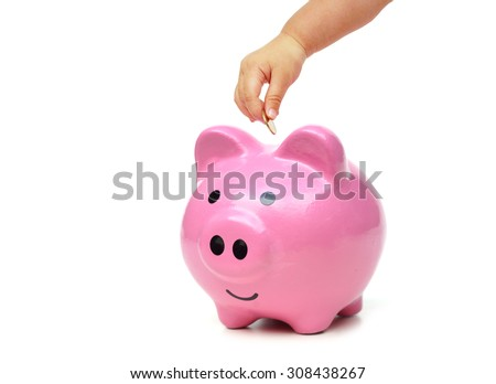 baby hand putting golden coins into a pink piggy - stock photo