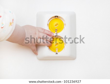 Baby hand reaching for an electrical outlet covered with yellow safety plugs (baby and child safety concept) - stock photo