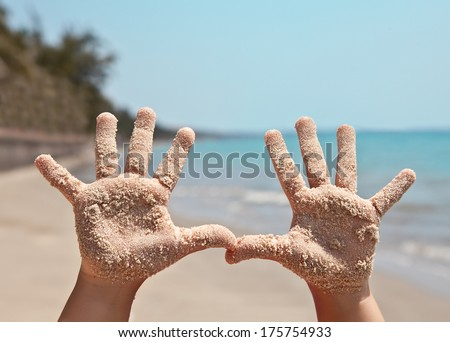 Baby handprints in the sand against sea landscape - stock photo