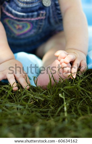 Baby Hands and Feet in the Grass - stock photo