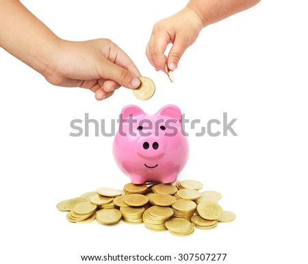 baby hands putting golden coins into a pink piggy bank with piles of golden coins  - saving money for security in life concept                      - stock photo