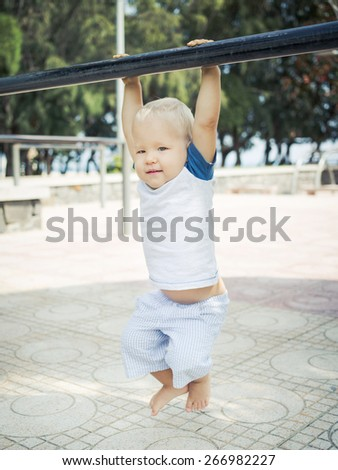 Baby hanging on a pull-up bar - stock photo