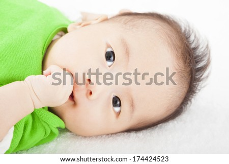 Baby having sucking  finger  and lying  on the towel - stock photo