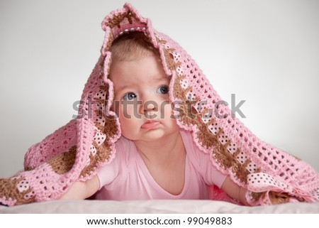 Baby hiding under blanket - stock photo