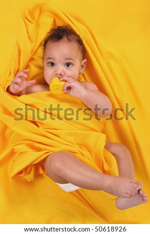 Baby Holding a Rubber Duckie Lying on Bright Yellow Background - stock photo