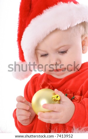 baby holding ornament with santa hat - stock photo