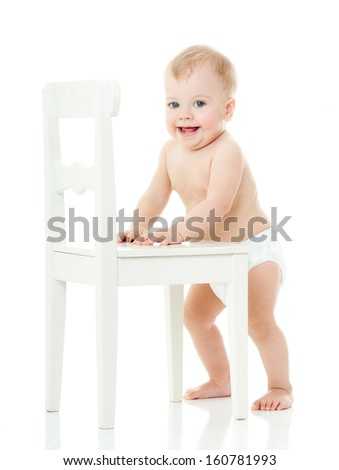 baby holds on to a white chair. isolated. - stock photo