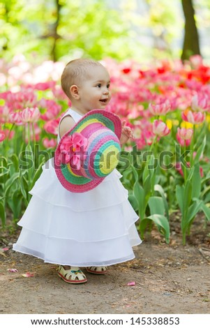 baby in an elegant dress near blossoming tulips - stock photo