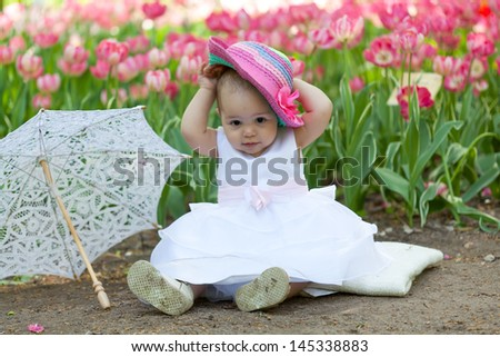 baby in an elegant dress with an umbrella sits near blossoming tulips - stock photo