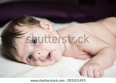 Baby in bed under the covers - stock photo