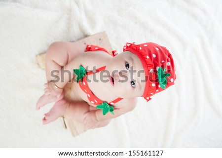 Baby in bikini, hat and sunglasses sitting look at camera - stock photo