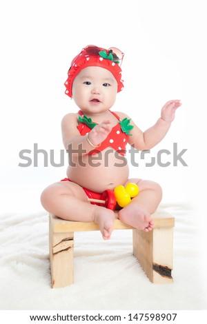 Baby in bikini, hat and sunglasses sitting on chair - stock photo