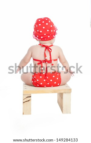 Baby in bikini, hat and sunglasses sitting on chair from behind - stock photo