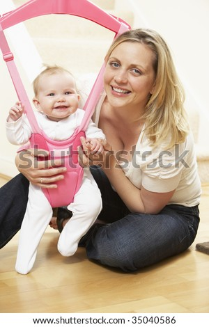 Baby In Bouncer With Mother - stock photo