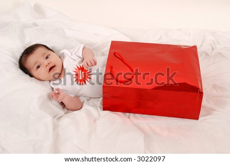 "baby in ""brand new"" body suit in gift bag - stock photo"