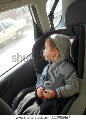 Baby in car seat for safety, looking outside - stock photo