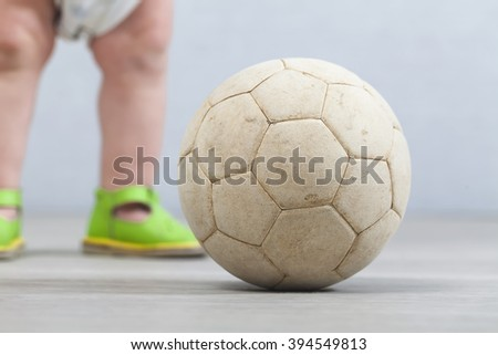 Baby in diaper and sandals in the background of a soccer ball - stock photo