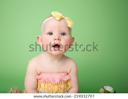 Baby in Easter outfit looking up, easter colors and flowers - stock photo