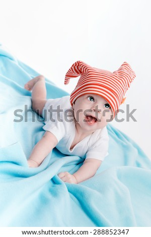 Baby in hat lying on a blue  - stock photo