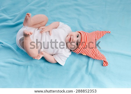 Baby in hat lying on a blue plaid - stock photo