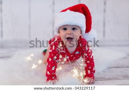 baby in red with cap playing with led lights - stock photo