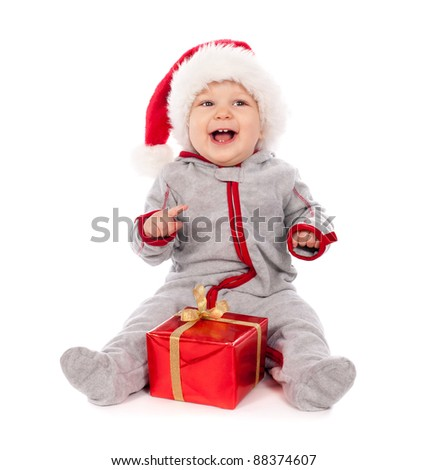 Baby in Santa hat playing with Christmas gift box isolated on white background - stock photo