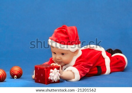 baby in santa's suit with gift and balls - stock photo