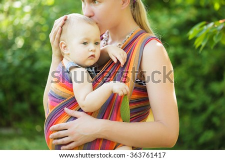 Baby in sling  - stock photo
