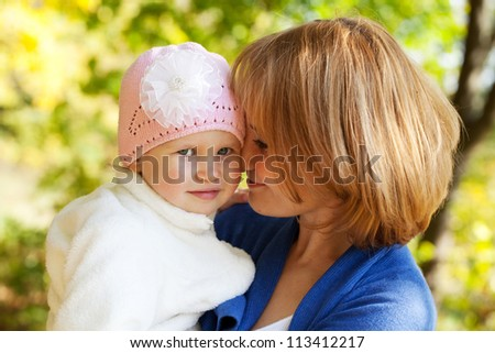 Baby in the arms of a young mother - stock photo