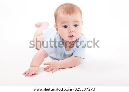 baby in the body lying on his stomach on a white background and looking at the camera, picture with depth of field - stock photo