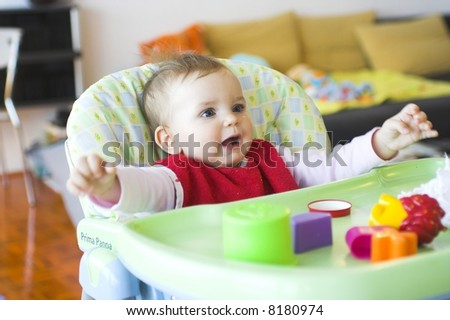 Baby in toddler seat - arms prepared to hug somebody - stock photo