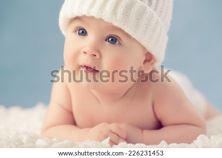 Baby in white winter hat lying on the floor - stock photo