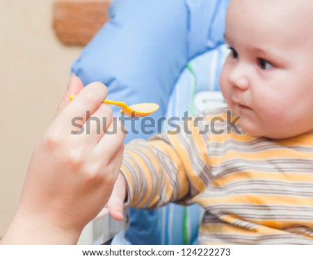Baby is being fed by her mum sitting on   high chair - stock photo
