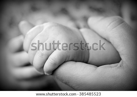 Baby is holding his mother's finger - stock photo
