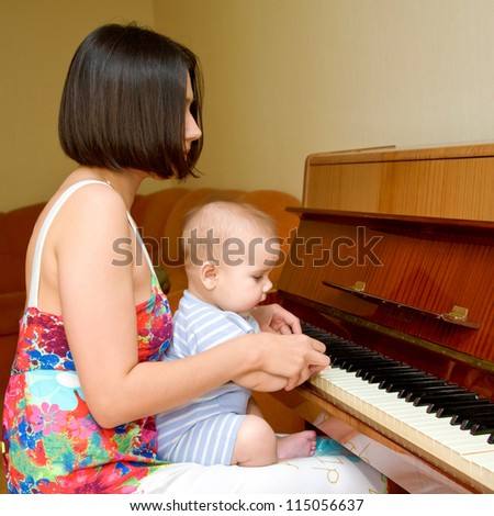 Baby is learning to play the piano. Mother helping him - stock photo