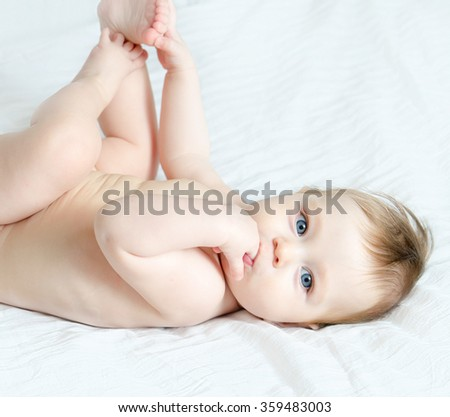 Baby is lying on his back and sucking his finger - stock photo